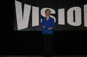 Jen Fong Speaking in front of Vision sign
